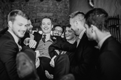 Wedding photojournalism groom carried by friends