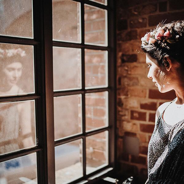 Hochzeitsfotograf_Vorbereitung_Braut_mit_Kranz_nachdenklich_romantisch_Sonnenstrahlen