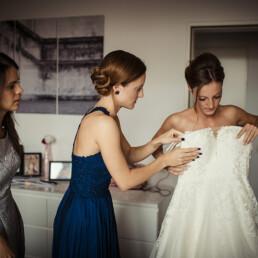 Wedding_getting_ready_bride_helped_with_wedding_dress