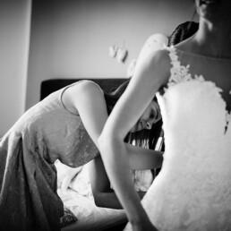Wedding_getting_ready_bride_helped_with_wedding_dress_bw