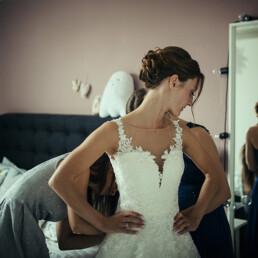 Wedding_getting_ready_bride_helped_with_wedding_dress_mirror