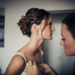 Wedding_getting_ready_bride_sister_helps_with_wedding_dress