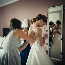 Wedding_getting_ready_friend_helps_with_wedding_dress