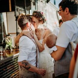 Hochzeitsfotograf_Berlin_Hochzeit_im_Osthafen_Brautpaar_nach_der_Zeremonie_Kuss_Baby