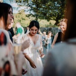Hochzeitsfotograf_Braut_nach_der_Zeremonie_Sekt_mit_Gaesten