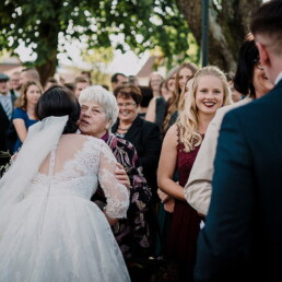 Hochzeitsfotograf_Brautpaar_nach_der_Zeremonie_vor_der_Kirche_Oma_gratuliert