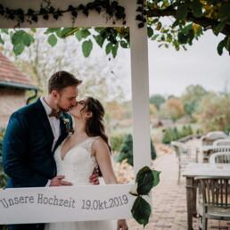 Hochzeitsfotograf_Fotosession_Brautpaar_Empfang_Kuss_mit_Rahmen