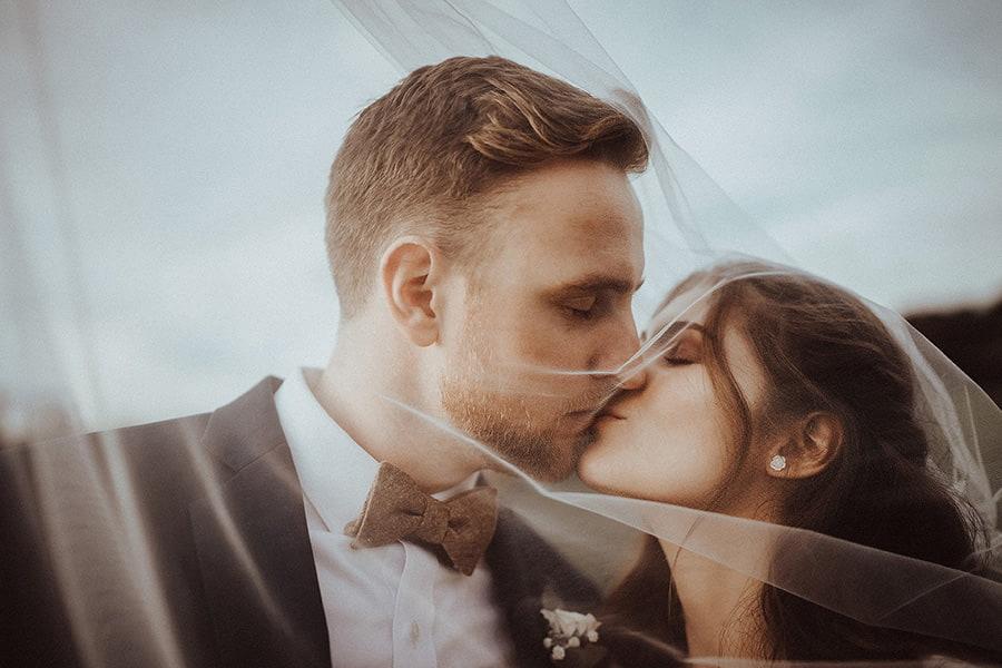 Hochzeitsfotograf_Fotosession_Brautpaar_romantischer_Kuss_mit_Brautschleier