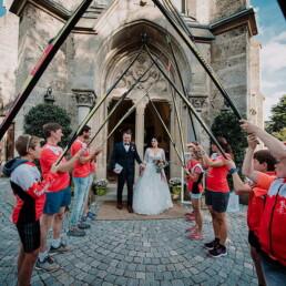 Hochzeitsfotograf_Zeremonie_Brautpaar_Ausgang_aus_der_Kirche_Gaeste_stehen_Skispalier