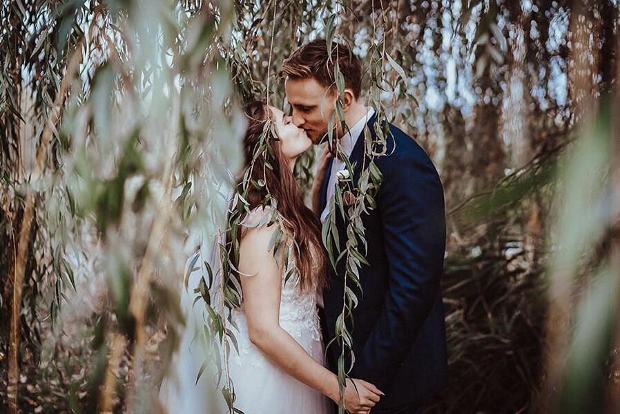 Hochzeitsfotograf_Zeremonie_im_Park_Brautpaar_romatisch_Weidenbaum