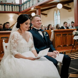 Hochzeitsfotograf_Zeremonie_in_einer_schoenen_Kirche_Braut_Braeutigam_laechelnd
