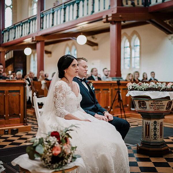 Hochzeitsfotograf_Zeremonie_in_einer_schoenen_Kirche_Brautpaar_Brautstrauss