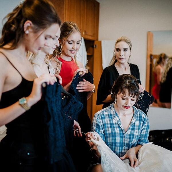 Hochzeitsfotografie_Vorbereitung_Freundinnen_bewundern_das_Brautkleid