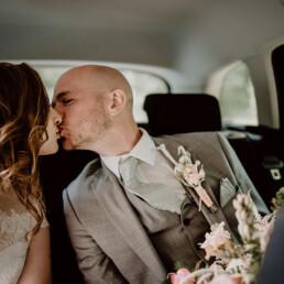 Hochzeitsfotografie_Zeremonie_Brautpaar_im_Auto_Kuss