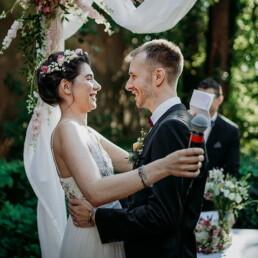 Hochzeitsfotografie_freie_Trauung_Brautpaar_vorm_Altar_Ehegeluebde_Mikrofon