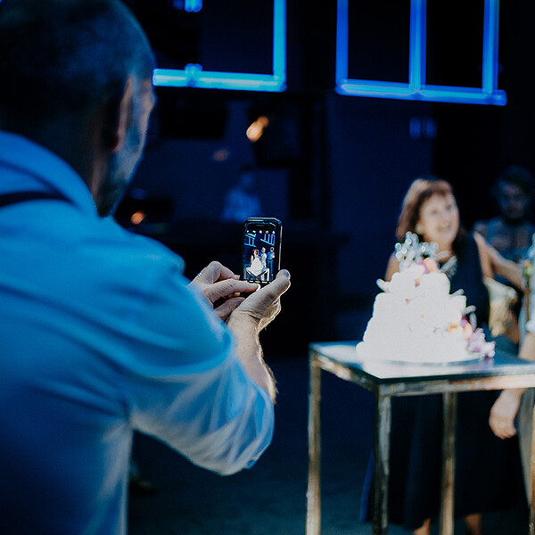 Wedding_photographer_reception_guest_taking_photo_mobile_phone