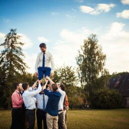 Wedding_photographer_reception_photosession_male_guests_carrying_the_groom