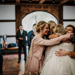 Wedding_photography_after_the_ceremony_friends_hugging_bride